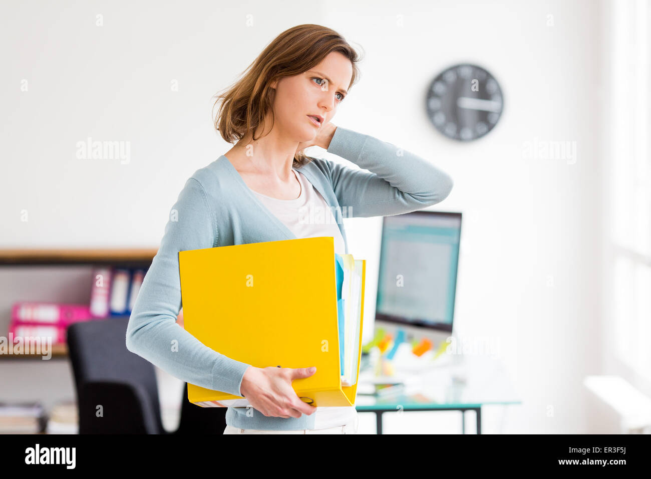 Woman suffering from neck pain in office. - Stock Image