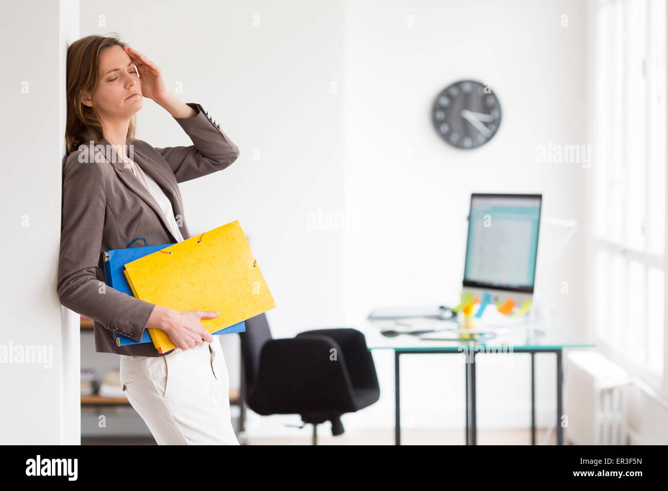 Woman at work suffering from headache. - Stock Image