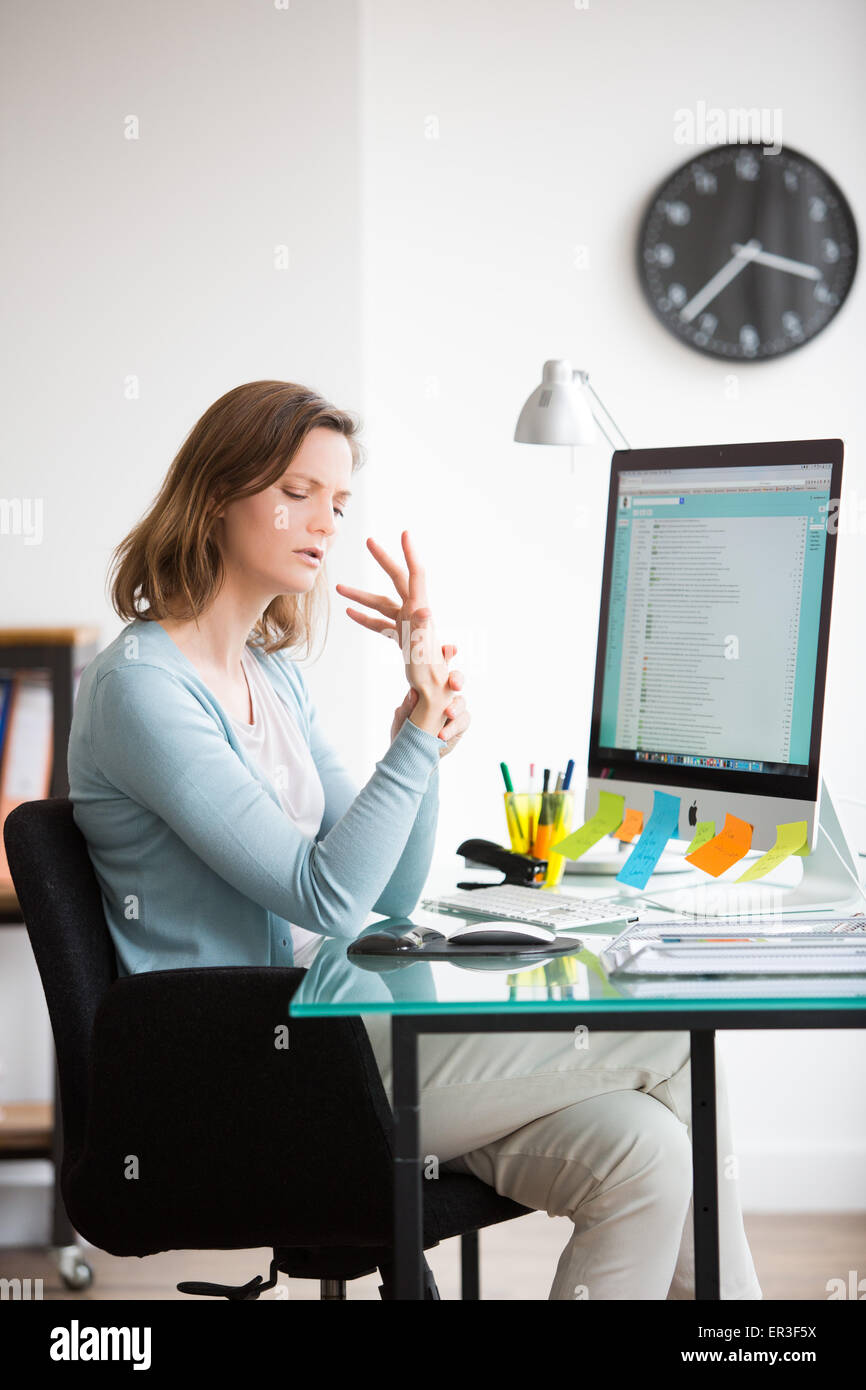 Woman at work suffering from wrist pain. - Stock Image