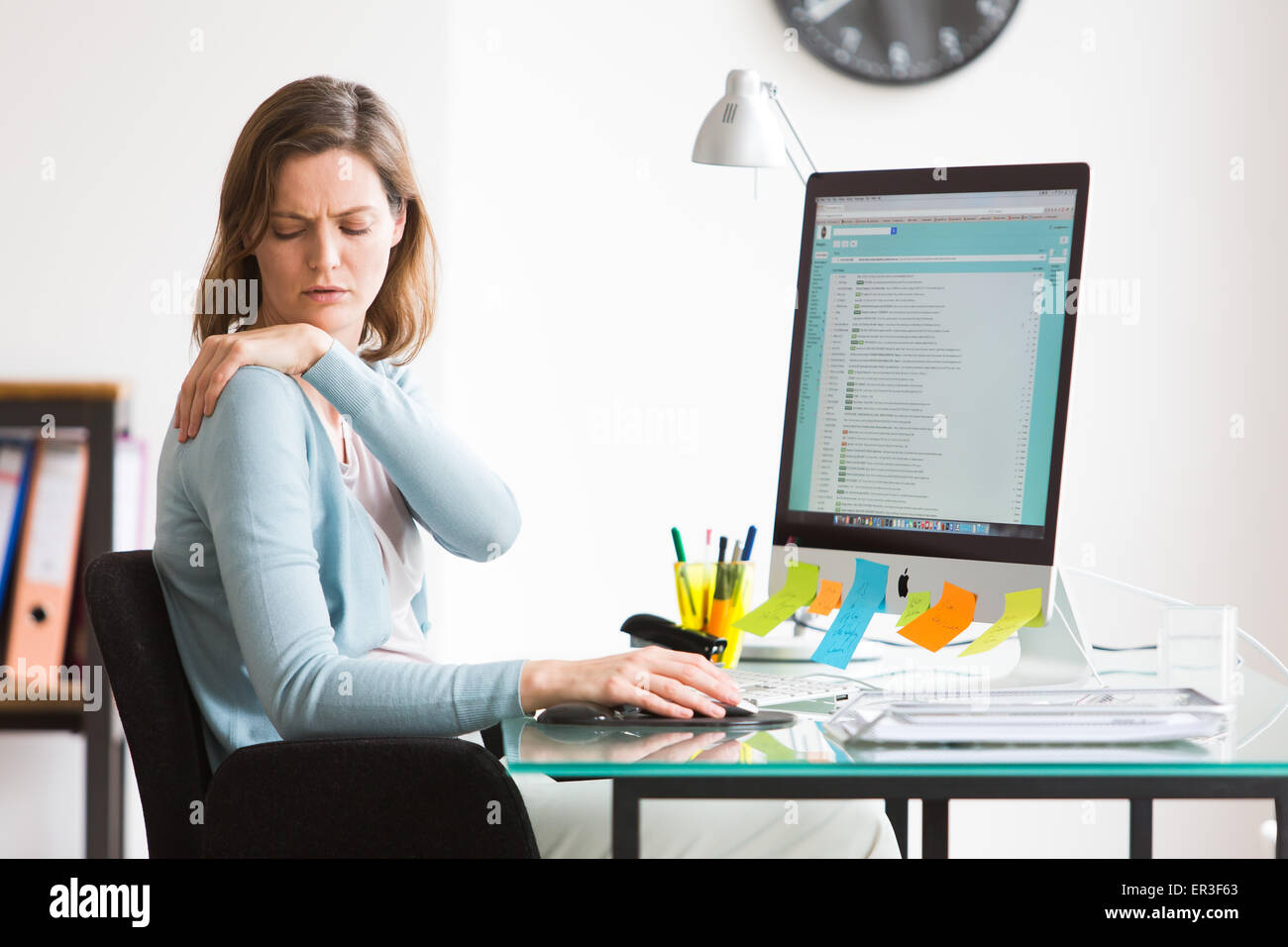 Woman at work suffering from shoulder pain. Stock Photo