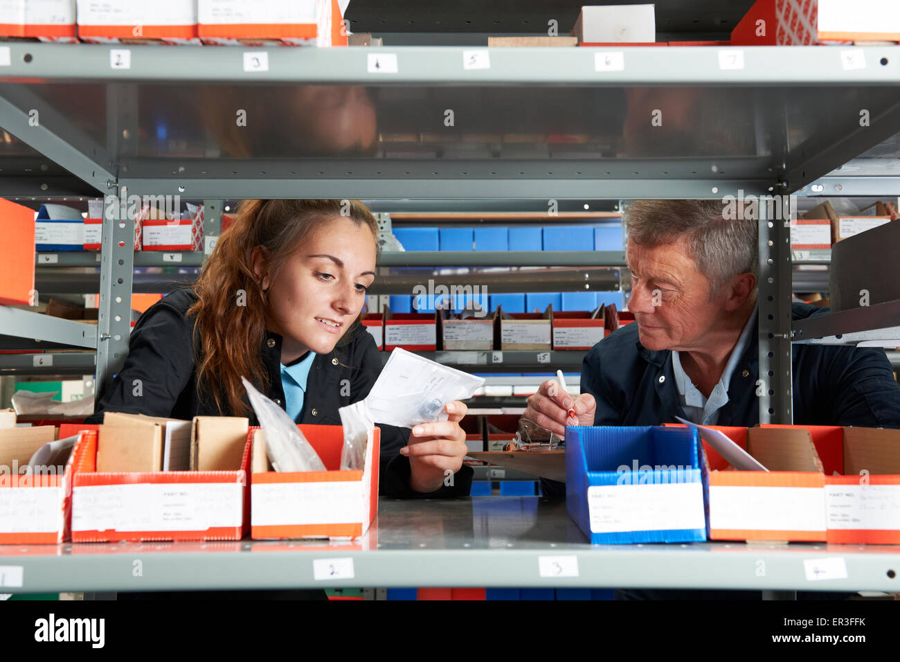 Male Engineer With Female Apprentice Checking Stock Levels - Stock Image