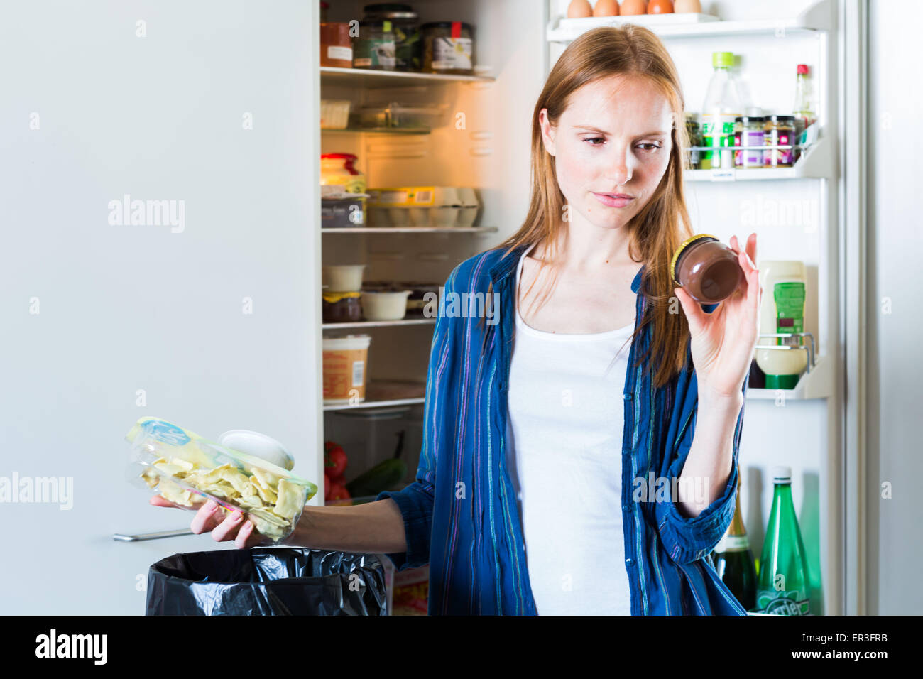 Woman throwing food in the trash. - Stock Image