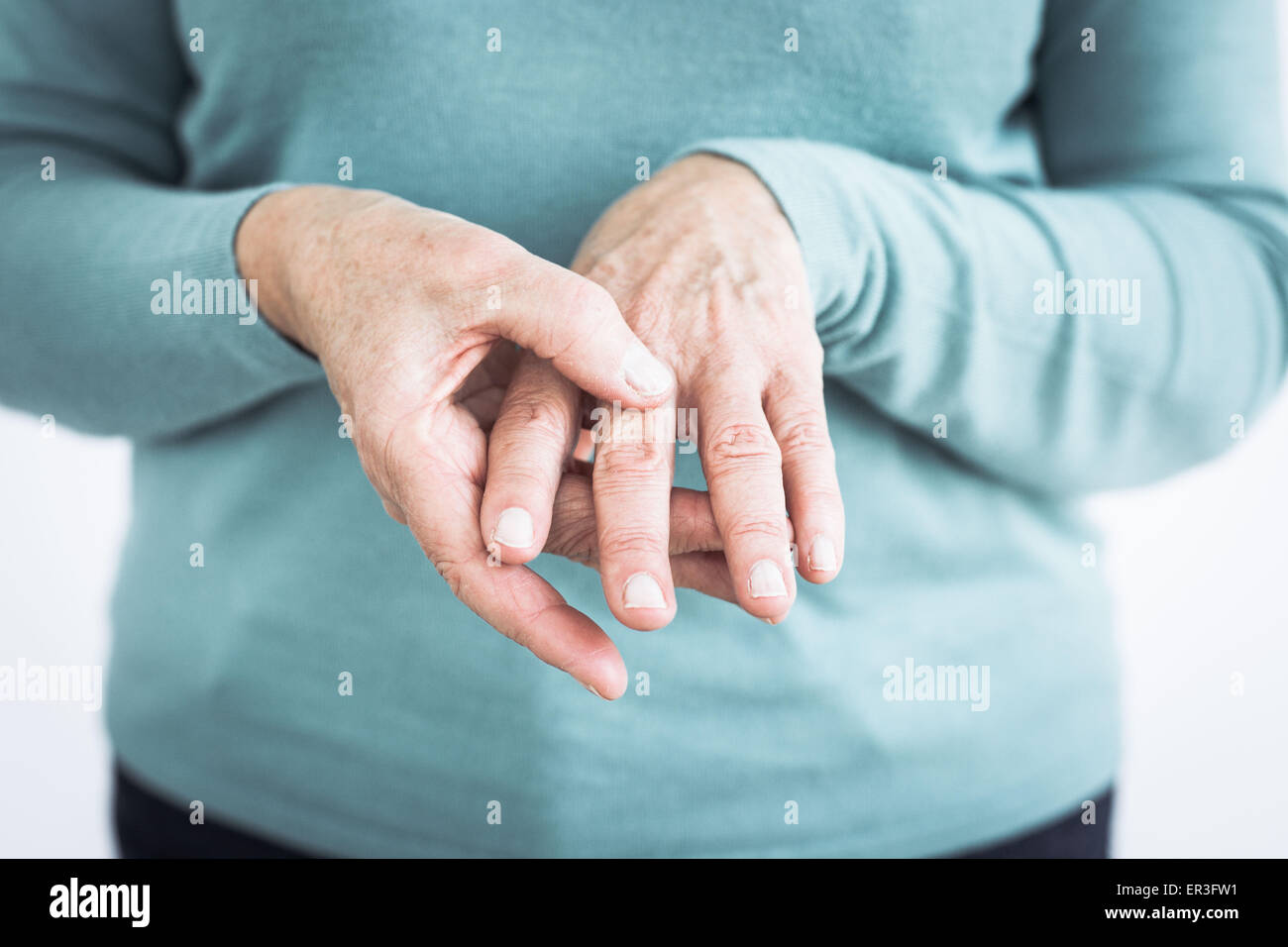Senior woman suffering from an articular pain in the hand. - Stock Image