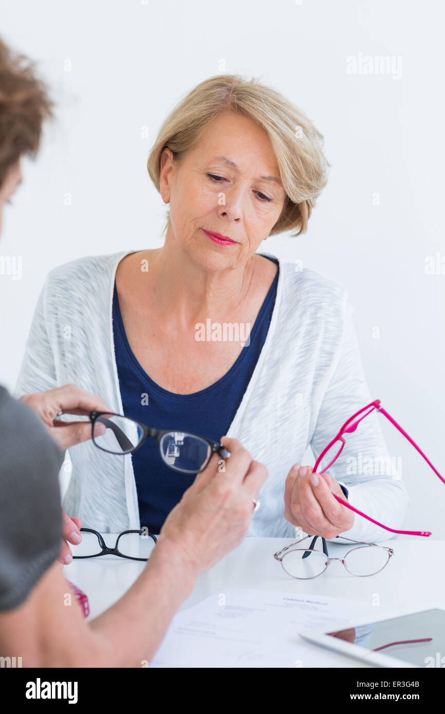 Woman trying eyeglasses. - Stock Image
