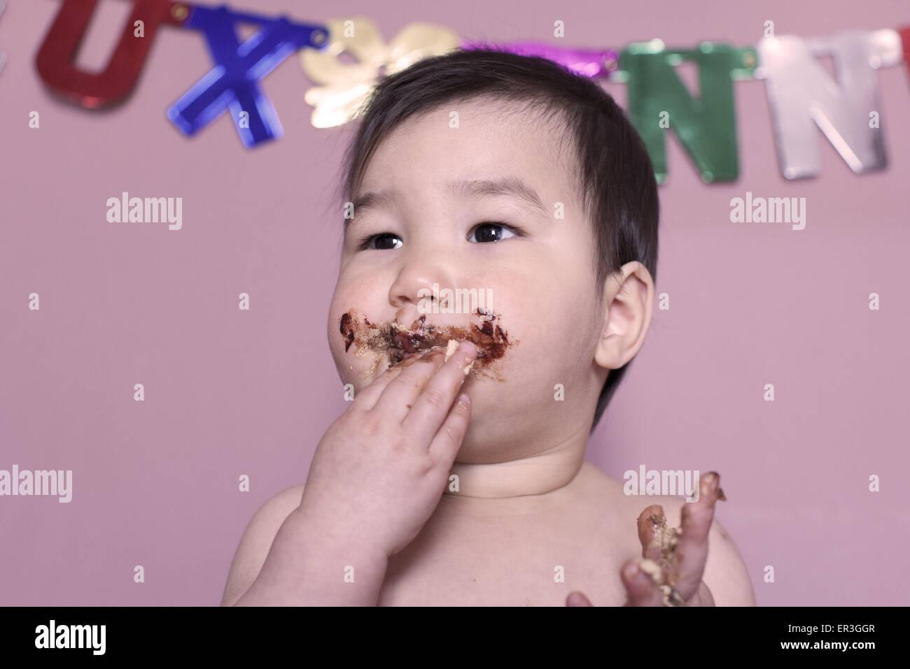 Baby eating birthday cake - Stock Image