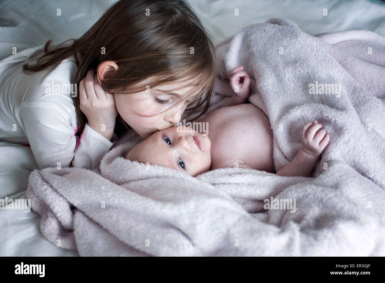 Little girl kissing baby brother's cheek on bed Stock Photo