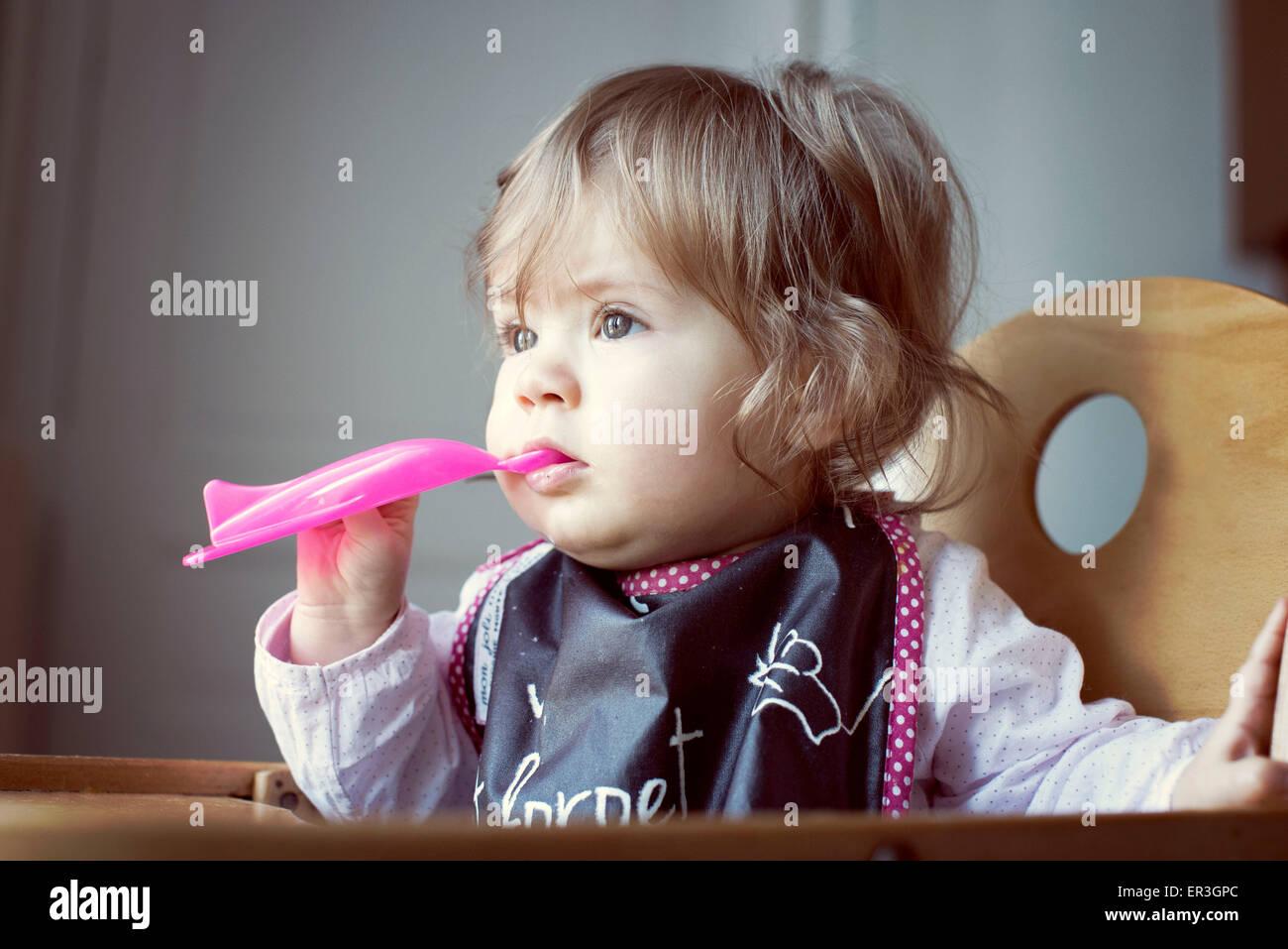 Baby girl feeding herself - Stock Image
