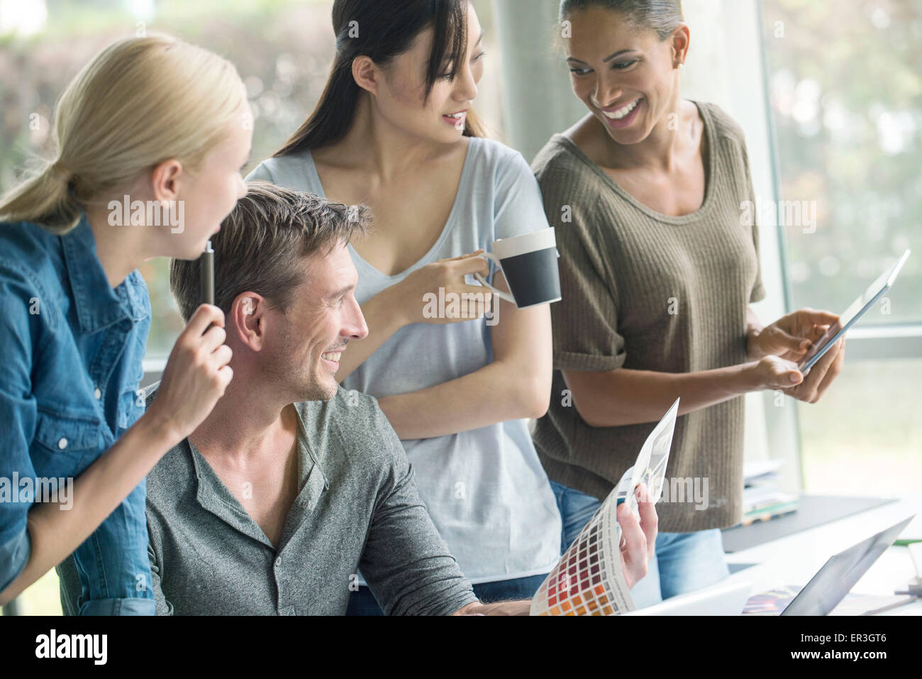 Colleagues having lighthearted time while browsing color swatch catalog - Stock Image