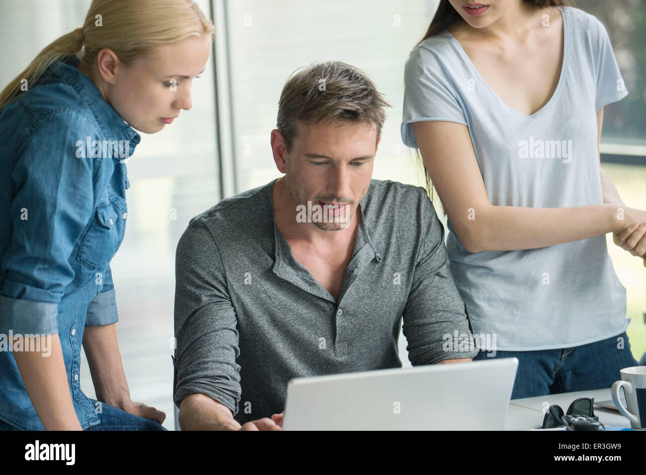 Workers gathered around desk of colleague - Stock Image