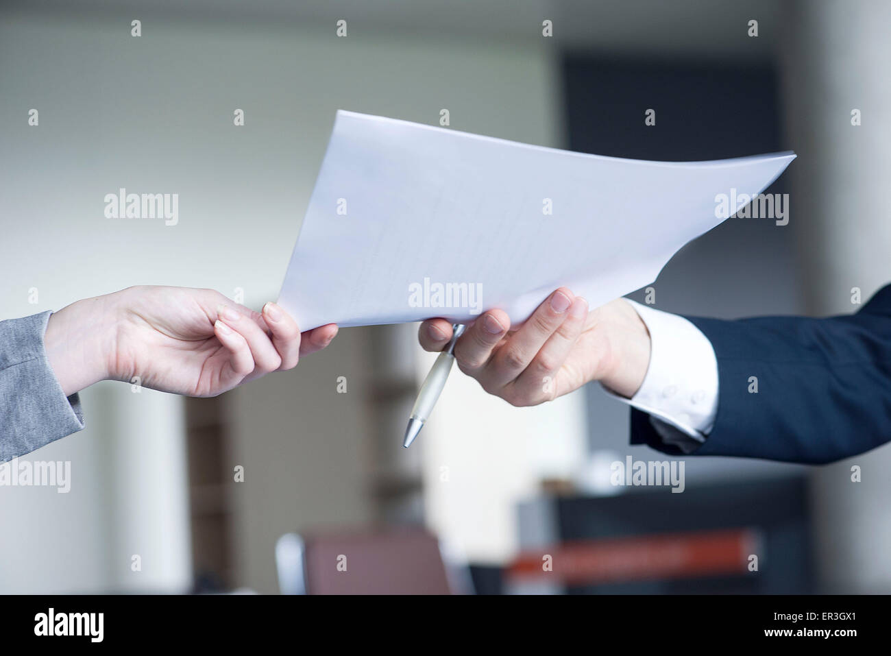 Businessman handing document to colleague, cropped - Stock Image
