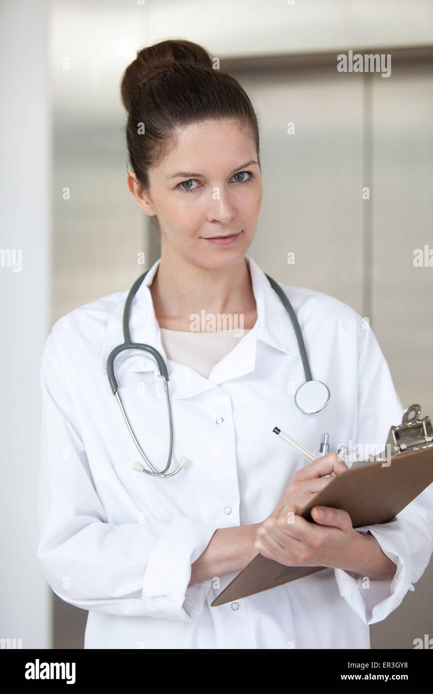 Doctor writing on medical chart, portrait - Stock Image
