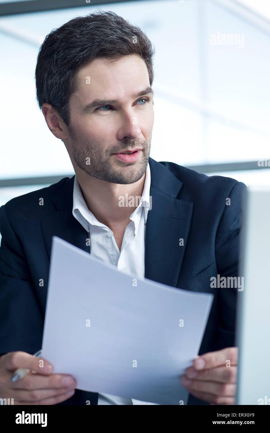 Businessman holding document - Stock Image