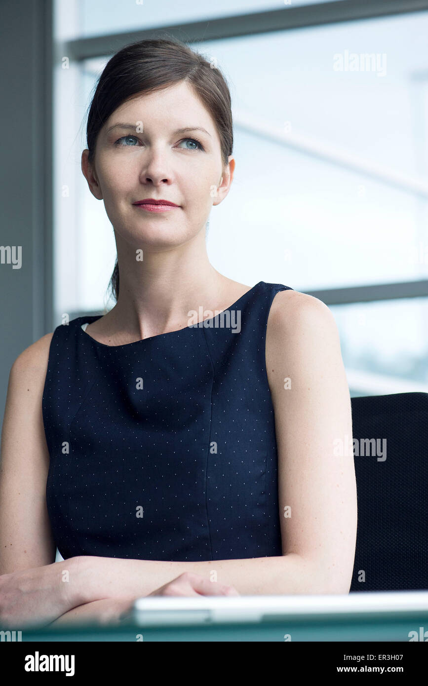 Businesswoman looking away in thought, portrait - Stock Image