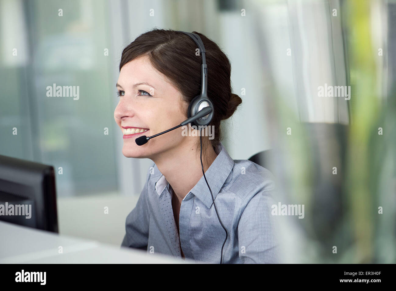 Receptionist wearing headset, smiling cheerfully - Stock Image
