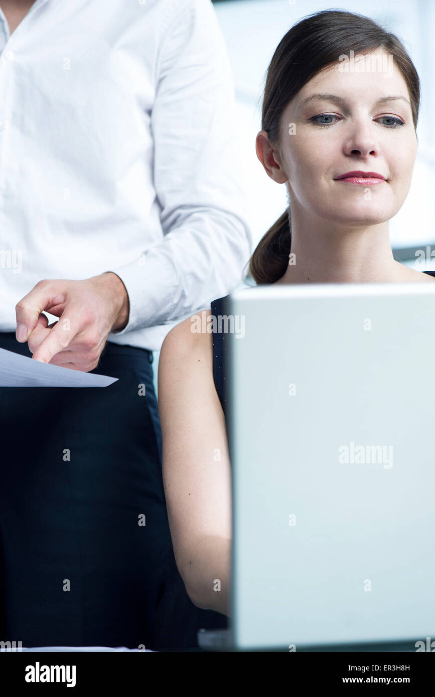 Woman working on laptop computer, boss watching over her shoulder - Stock Image