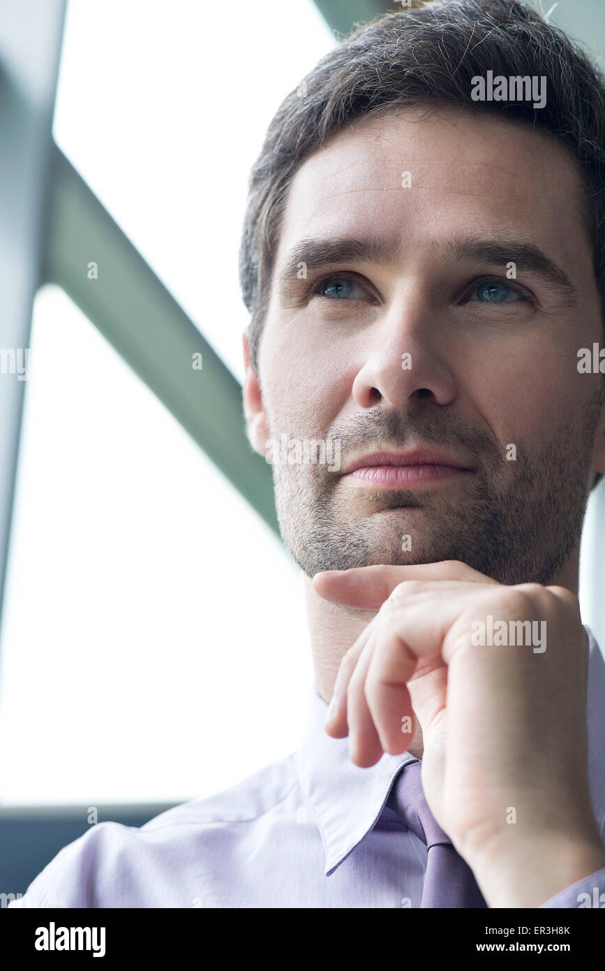 Businessman looking up in thought, portrait - Stock Image