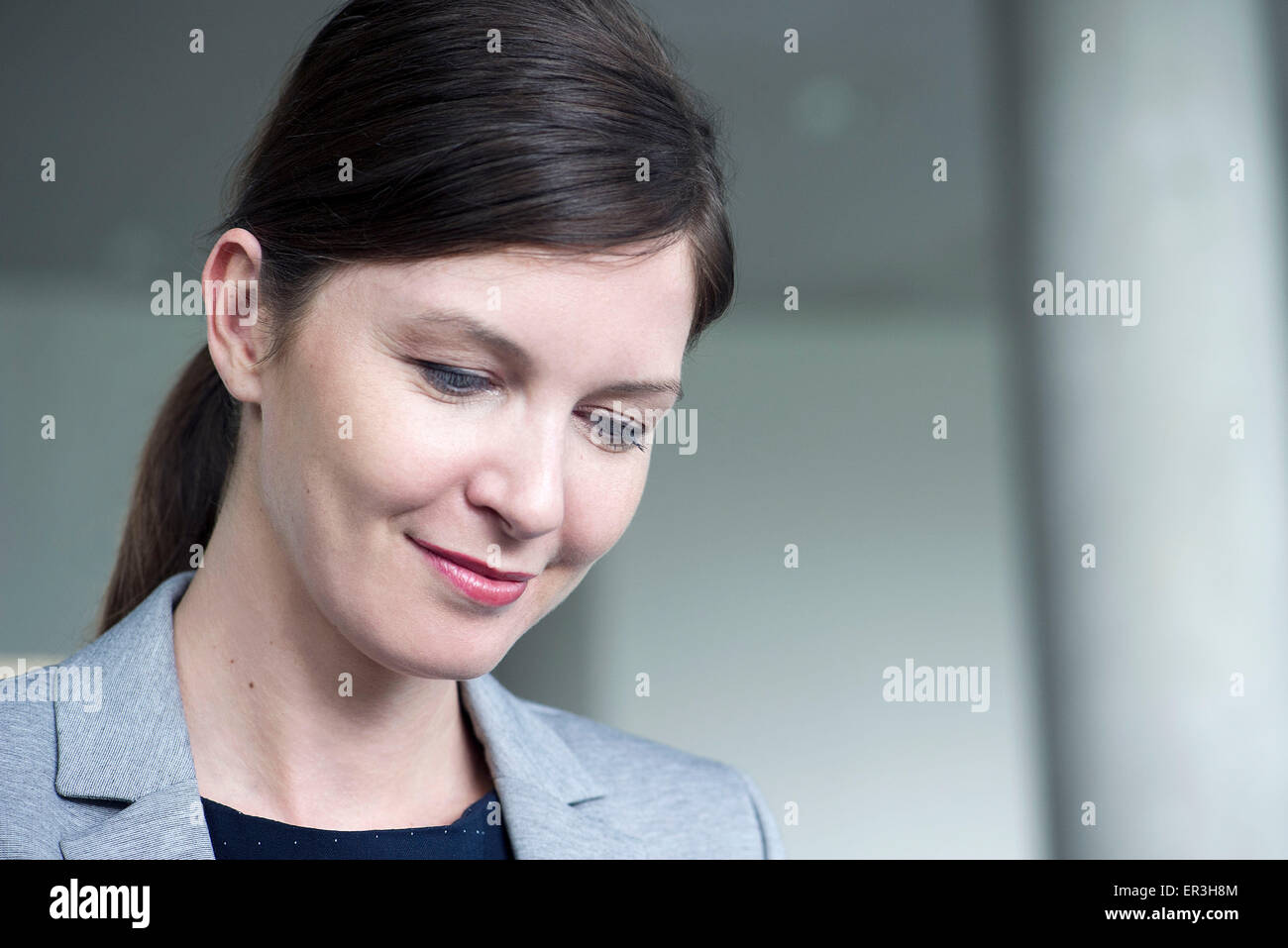 Businesswoman looking down in thought, smiling - Stock Image
