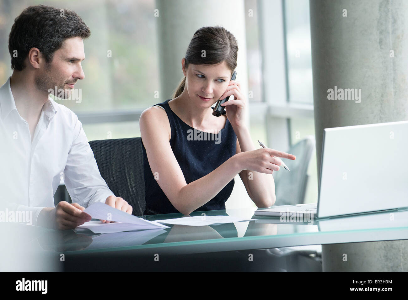 Businesswoman directing colleague's attention to computer screen - Stock Image