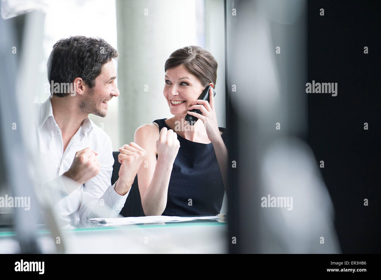 Business associates pleased by good news phone call - Stock Image