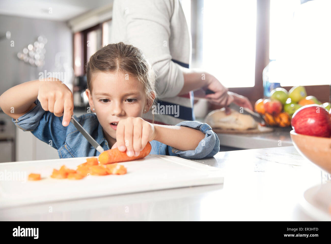 Little girl helping to prepare food in kitchen - Stock Image