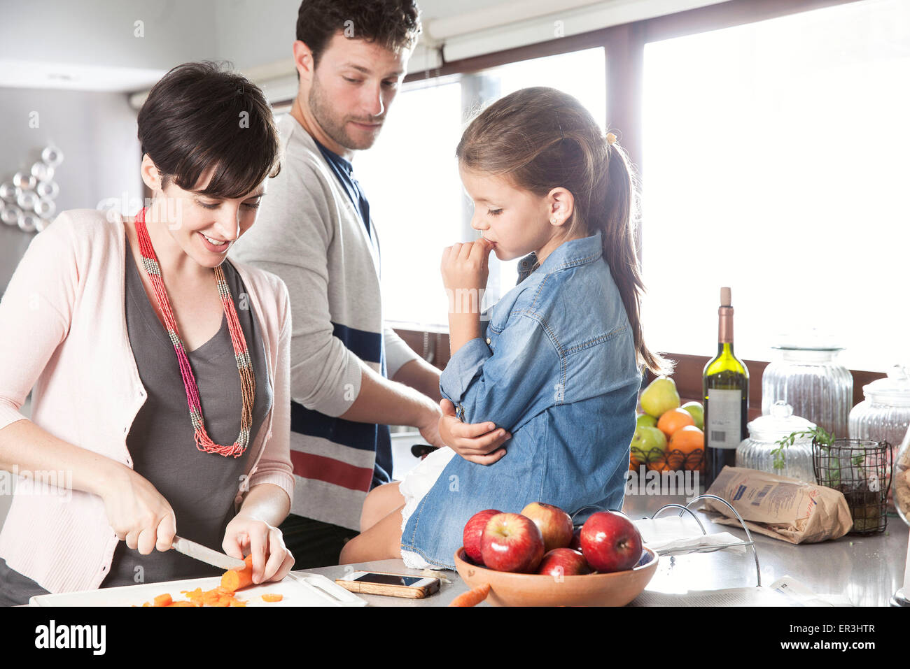 Family preparing food together in kitchen - Stock Image