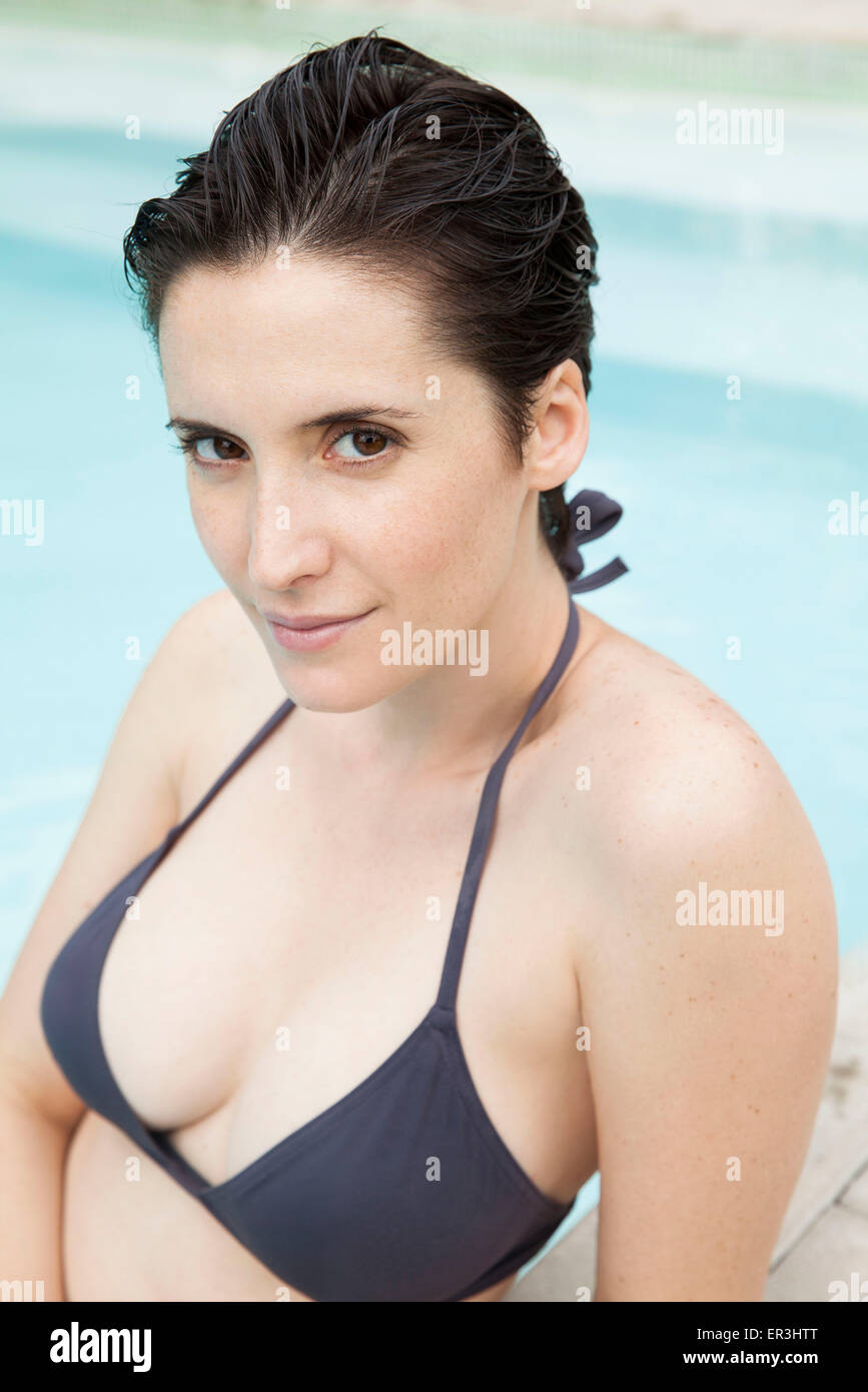 Woman relaxing in pool, portrait - Stock Image