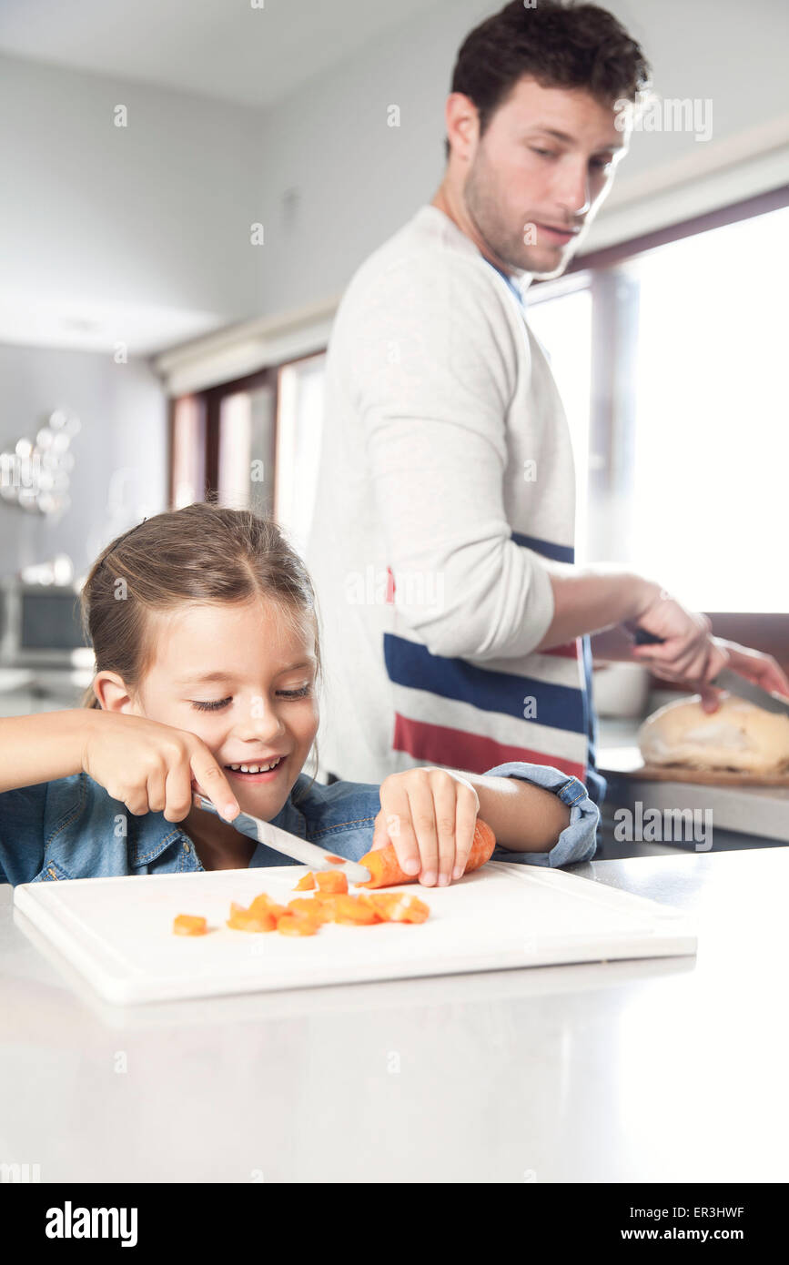 Little girl helping her father prepare food in kitchen - Stock Image