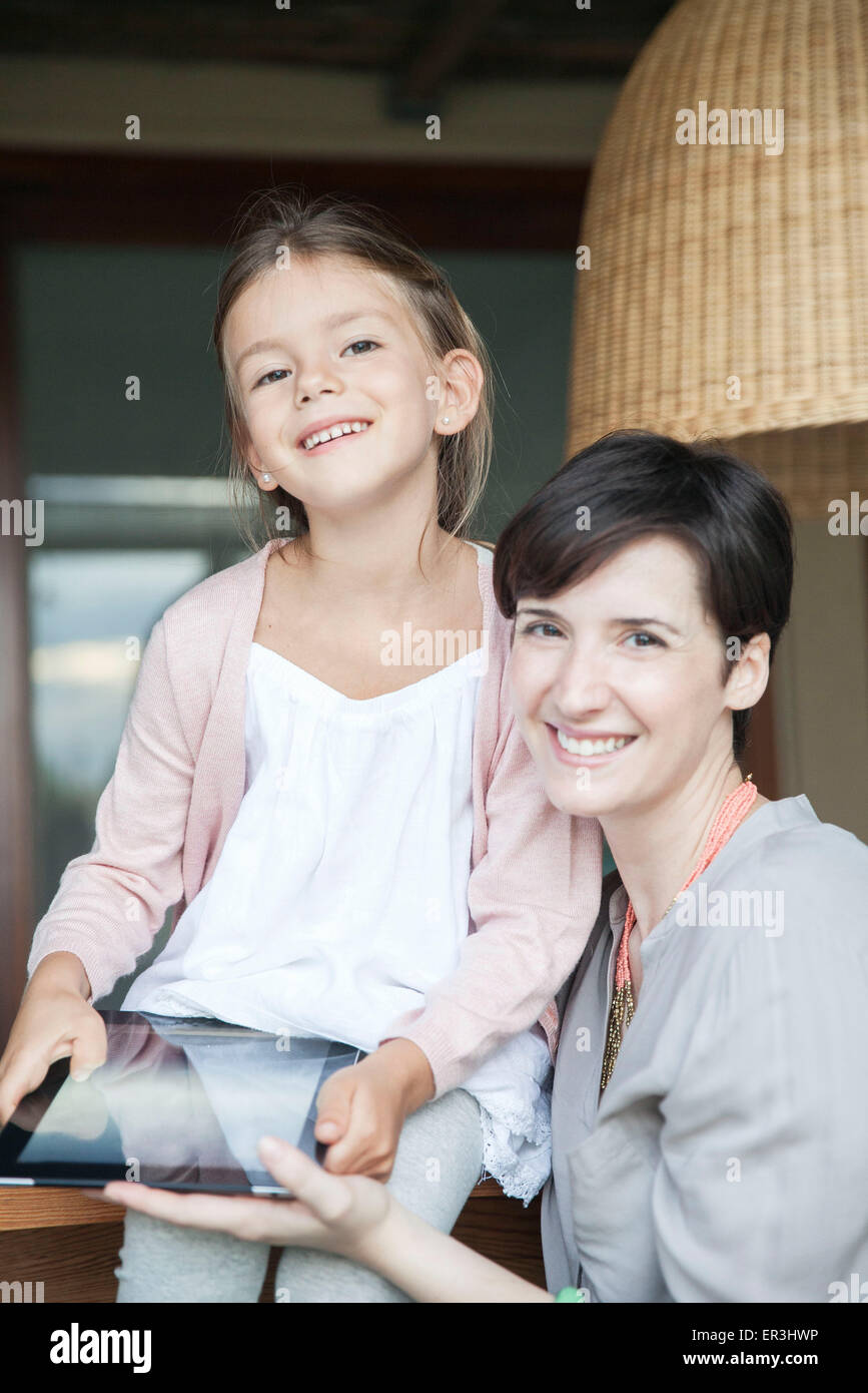 Mother and young daughter using digital tablet together - Stock Image