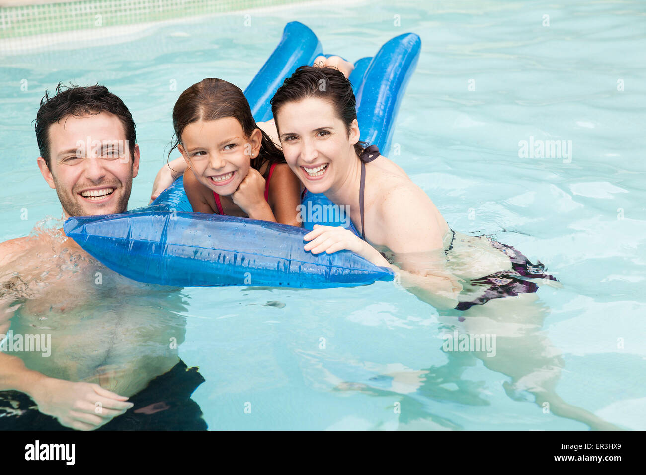 Family playing together in pool - Stock Image