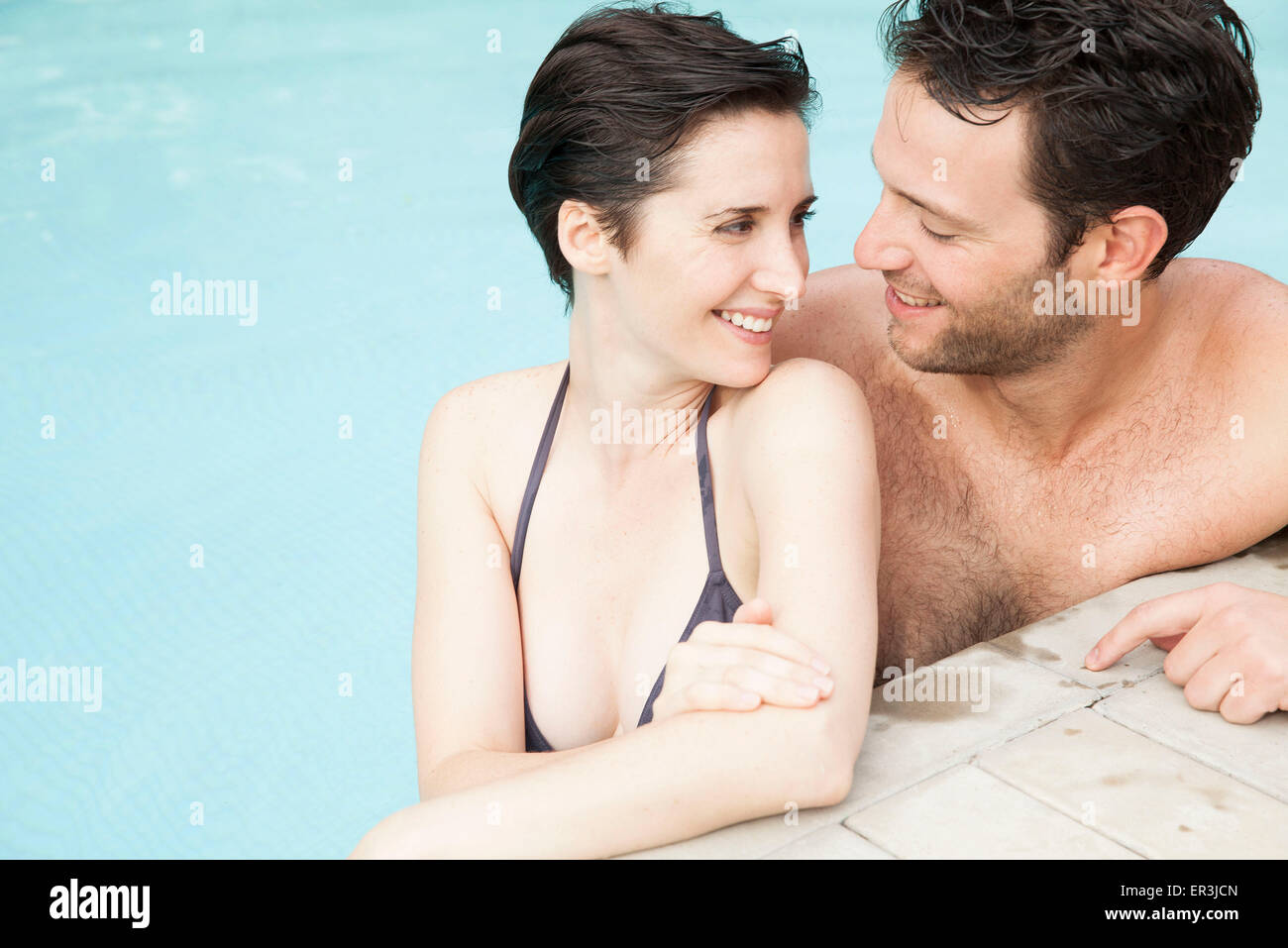 Couple relaxing together in pool - Stock Image