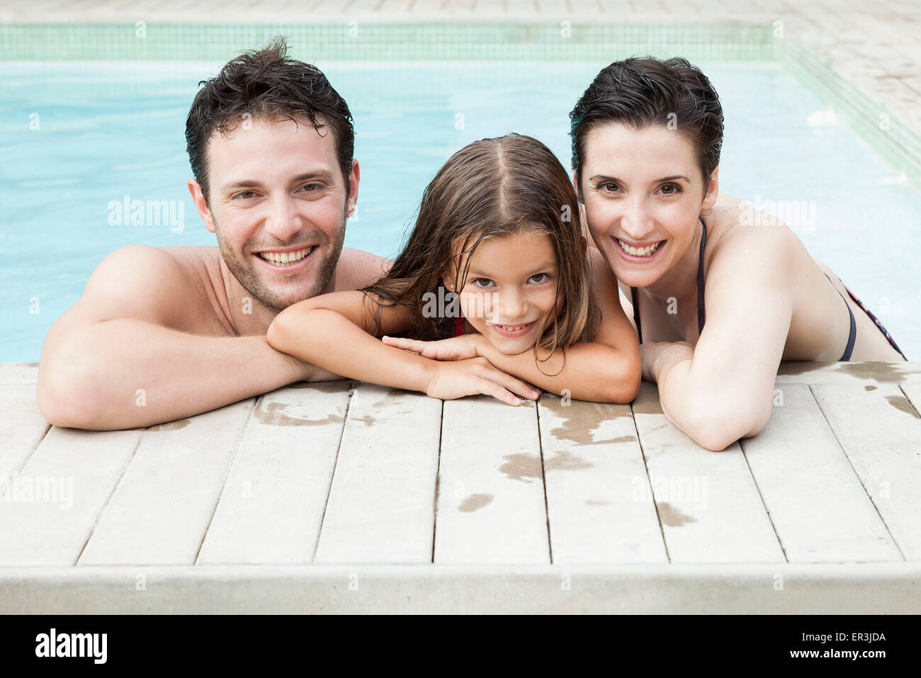 Family relaxing together in pool, portrait - Stock Image