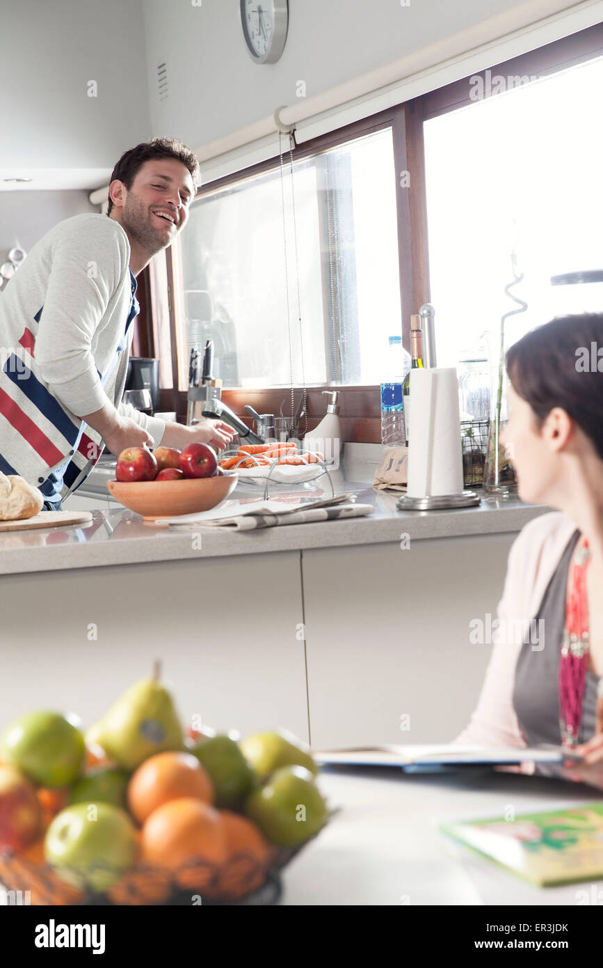 Couple talking together in kitchen - Stock Image