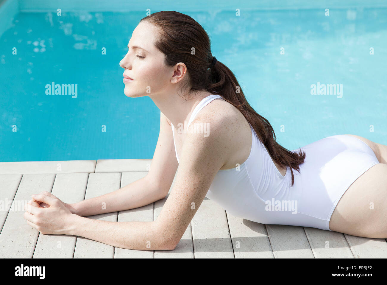Young woman sunbathing beside pool with eyes closed - Stock Image