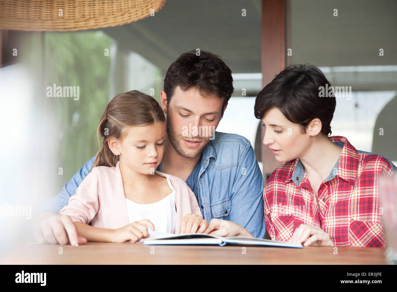 Little girl reading with her parents - Stock Image