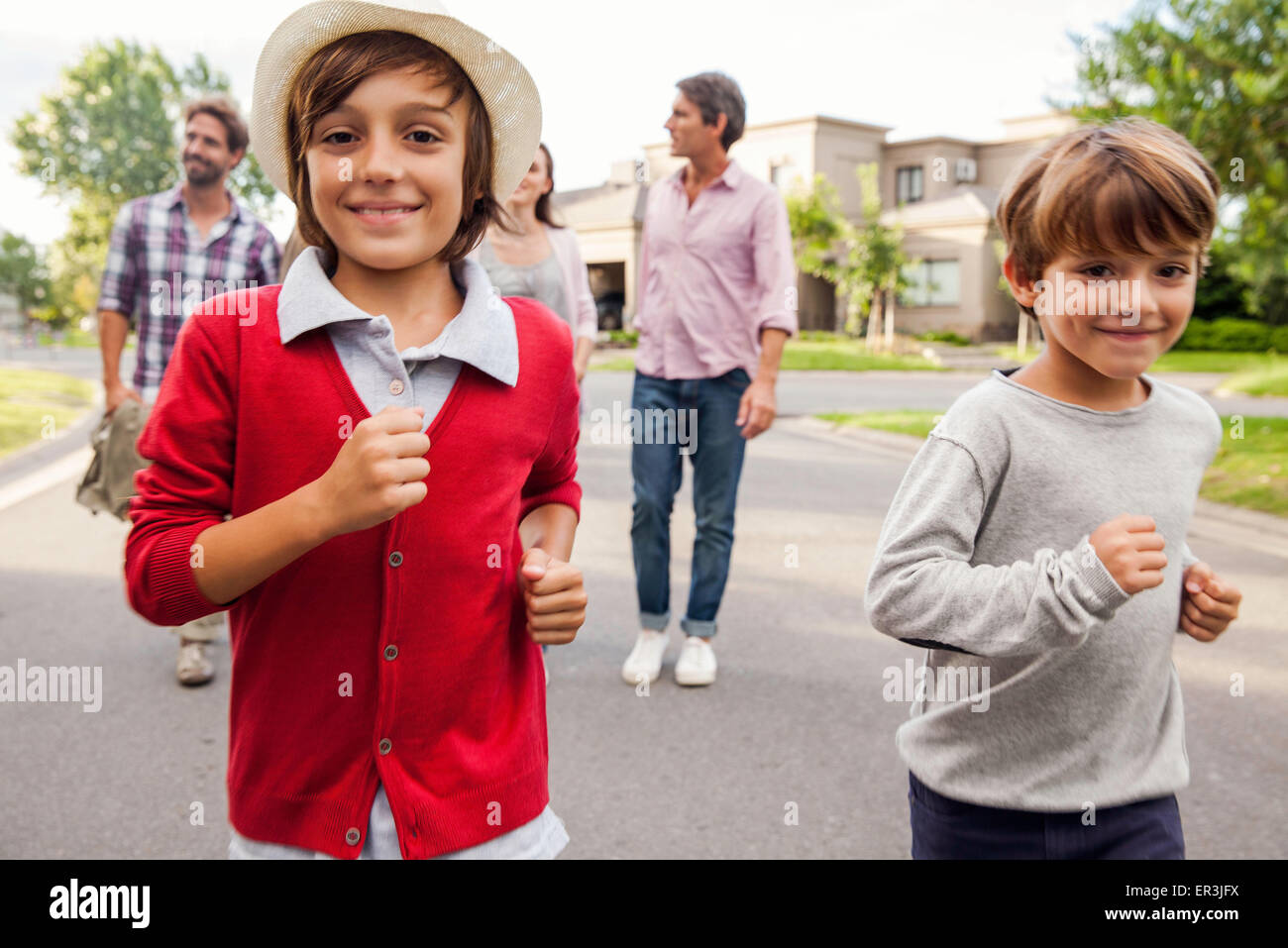 Boys running outdoors, family in background - Stock Image