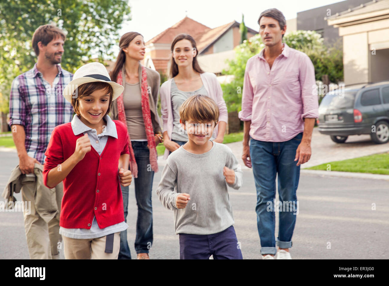 Family walking together through suburban neighborhood - Stock Image