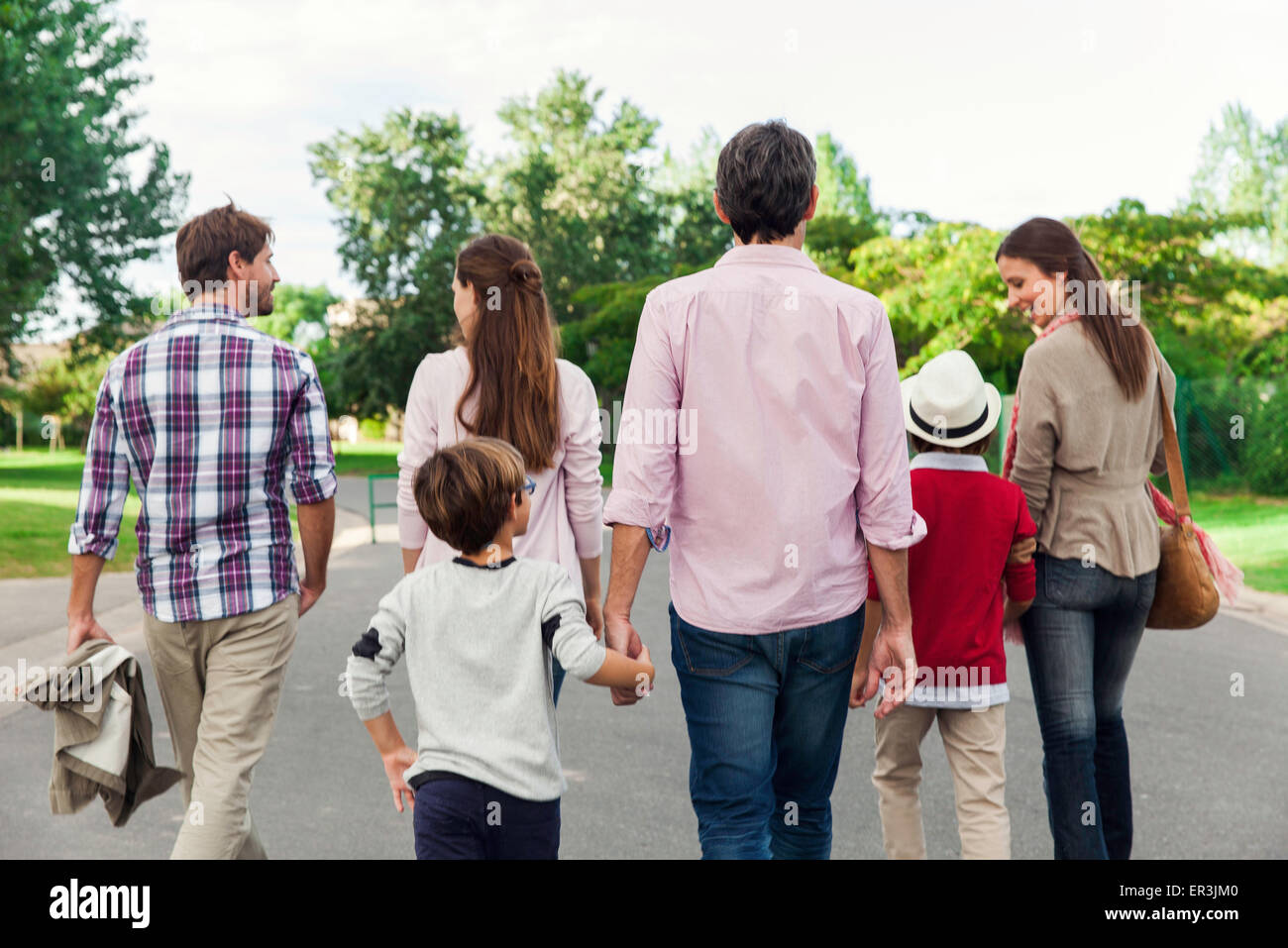 Family walking together outdoors, rear view - Stock Image
