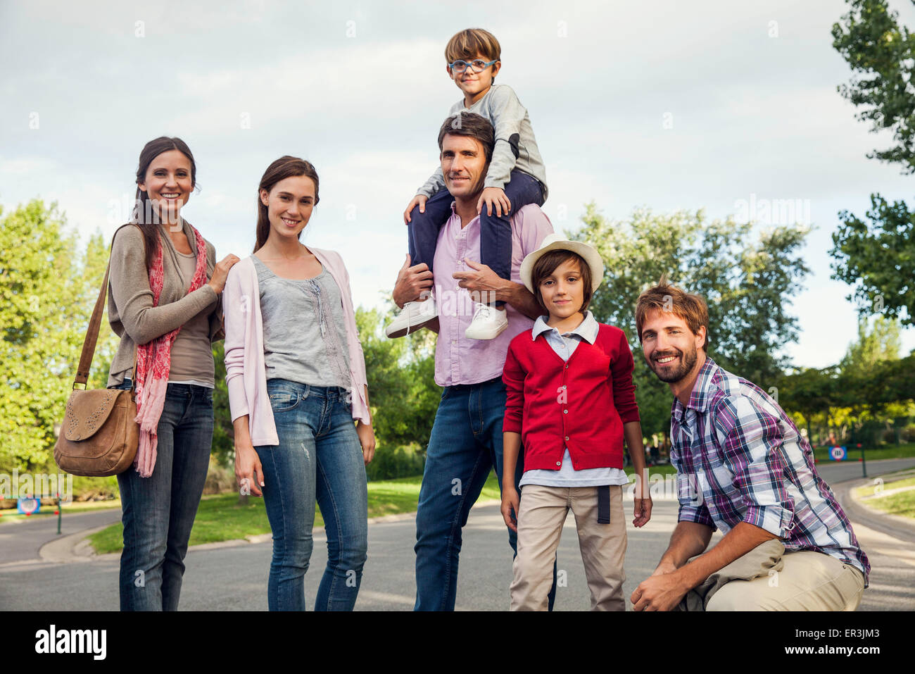 Family posing for group portrait outdoors - Stock Image