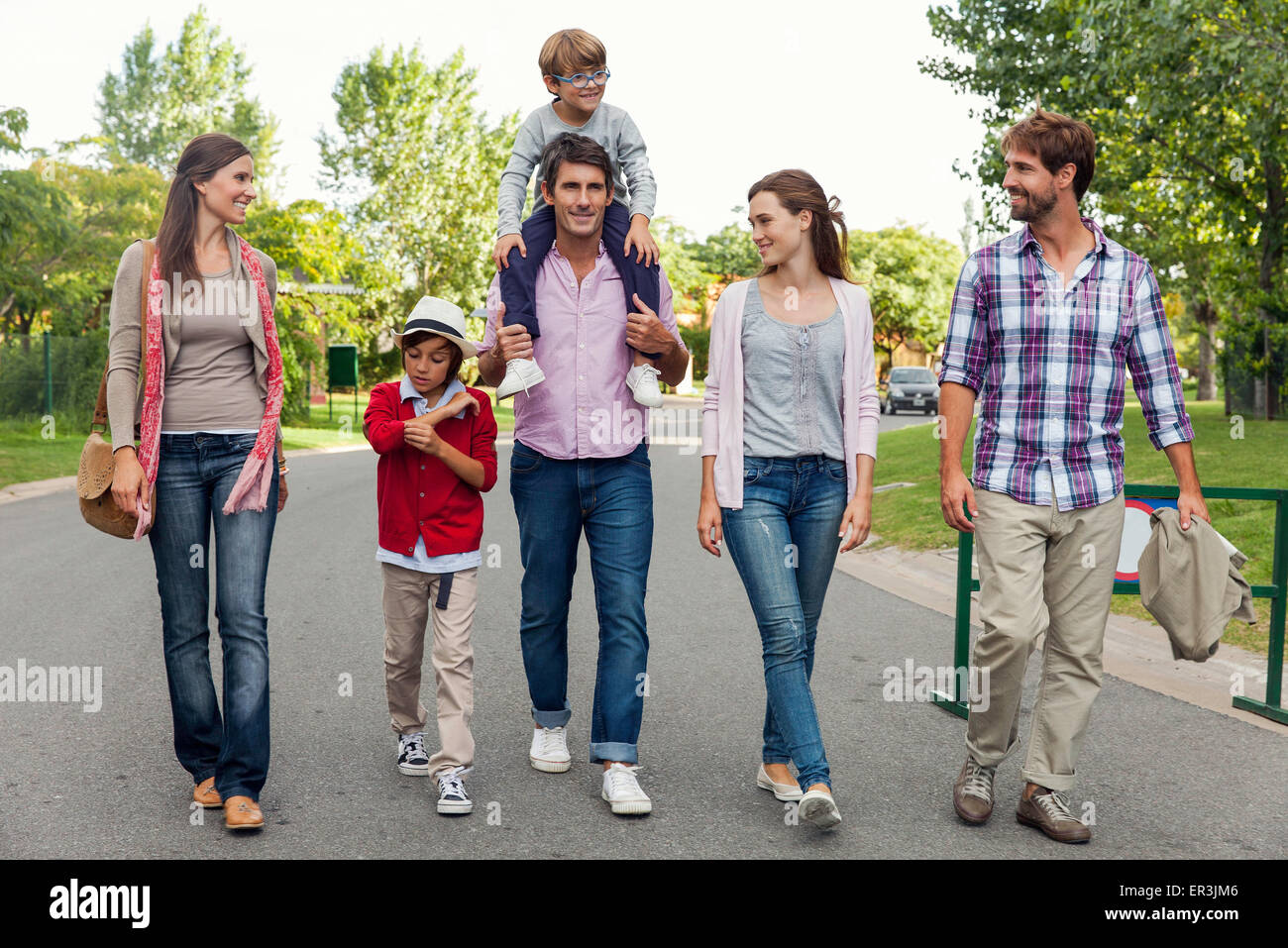 Family walking together in street - Stock Image