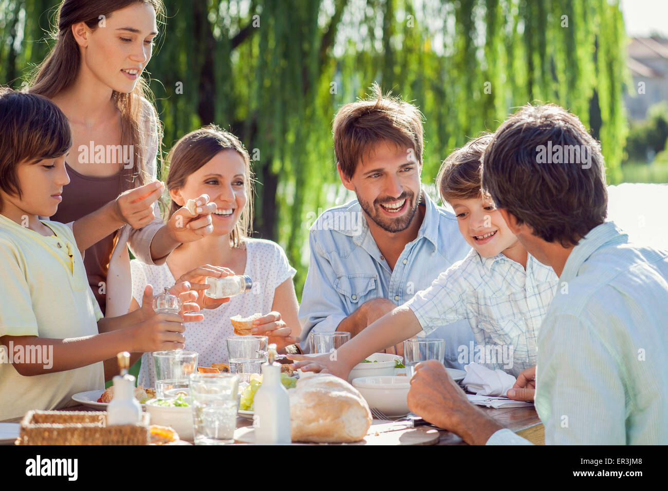 Family enjoying breakfast together outdoors - Stock Image