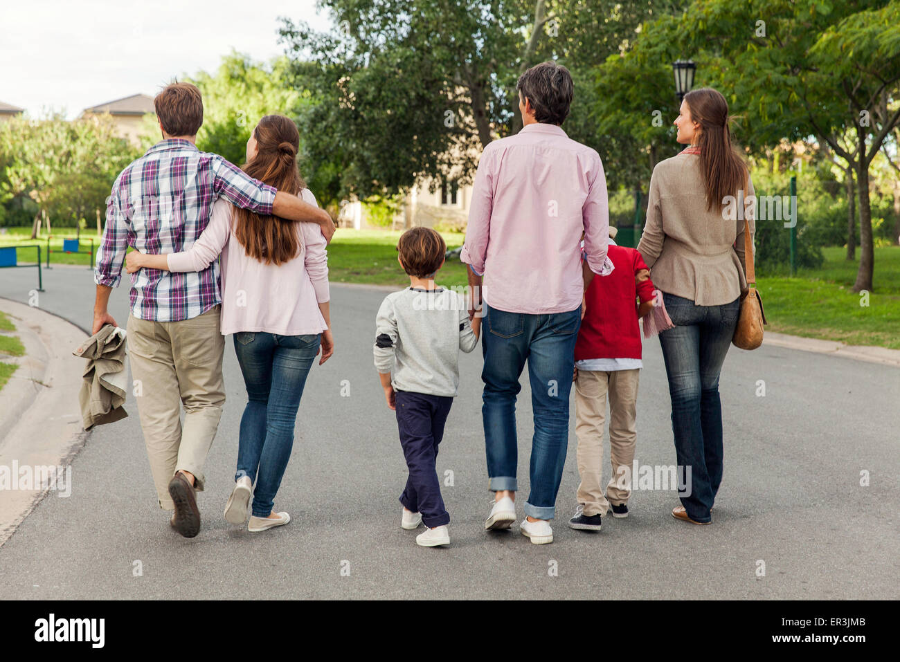 Family walking together in street, rear view - Stock Image