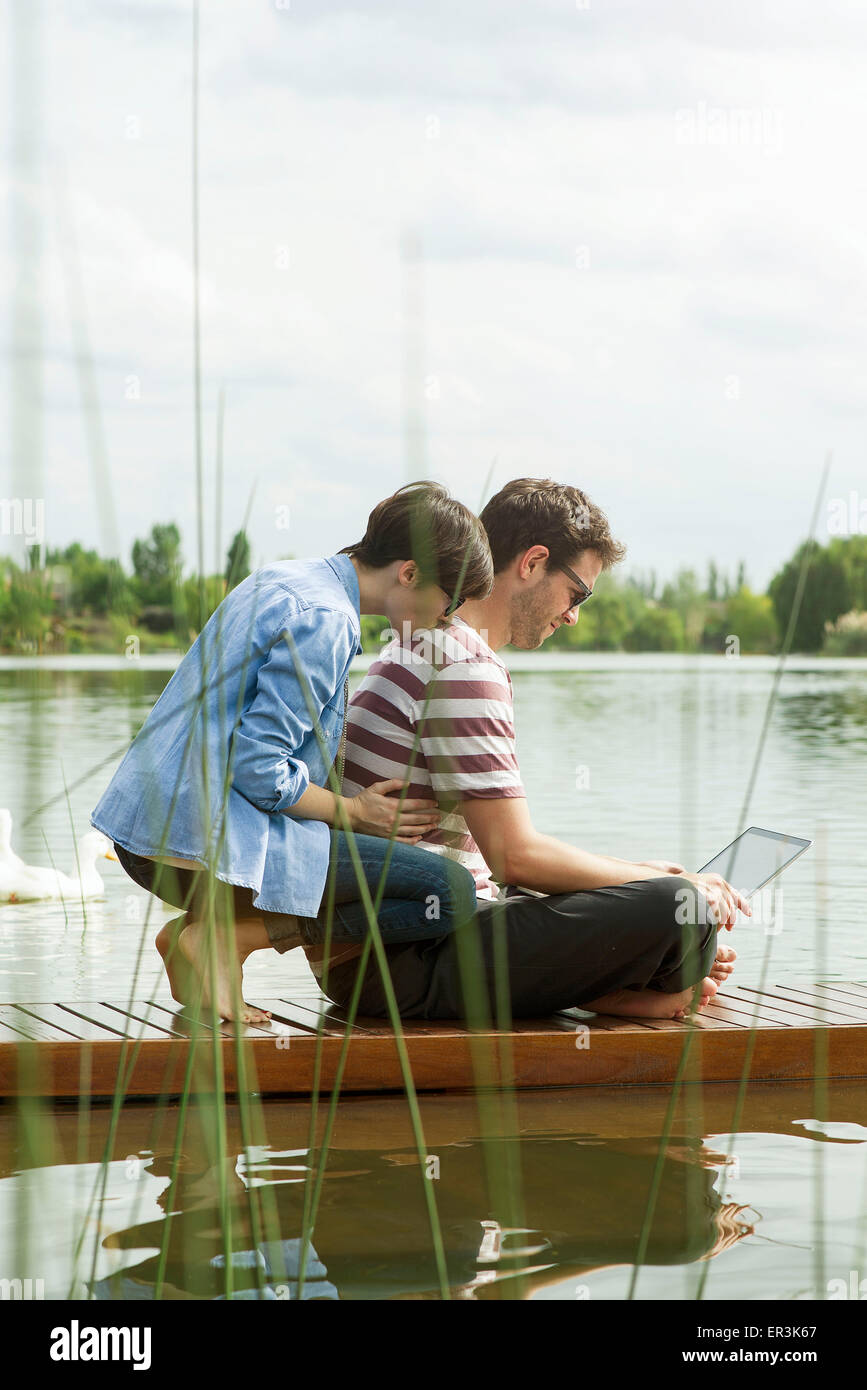 Couple using laptop computer on dock - Stock Image
