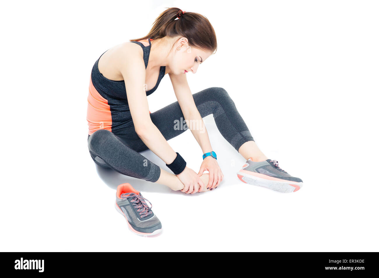 Portrait of a sporty woman with pain on leg isolated on a white background - Stock Image