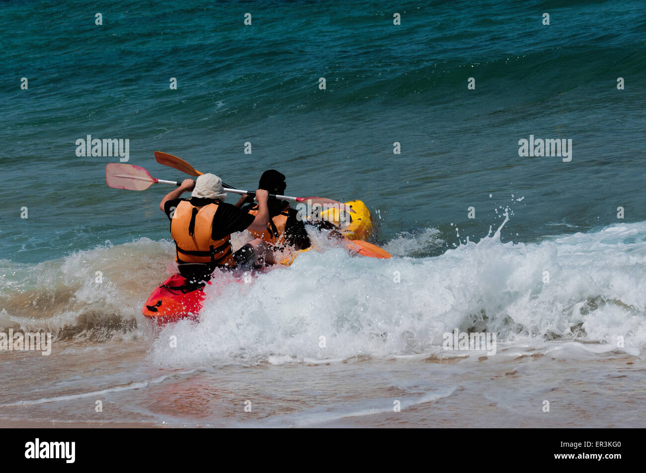 Two athletes compete in the kayak with sea waves trying to swim away from the shore - Stock Image