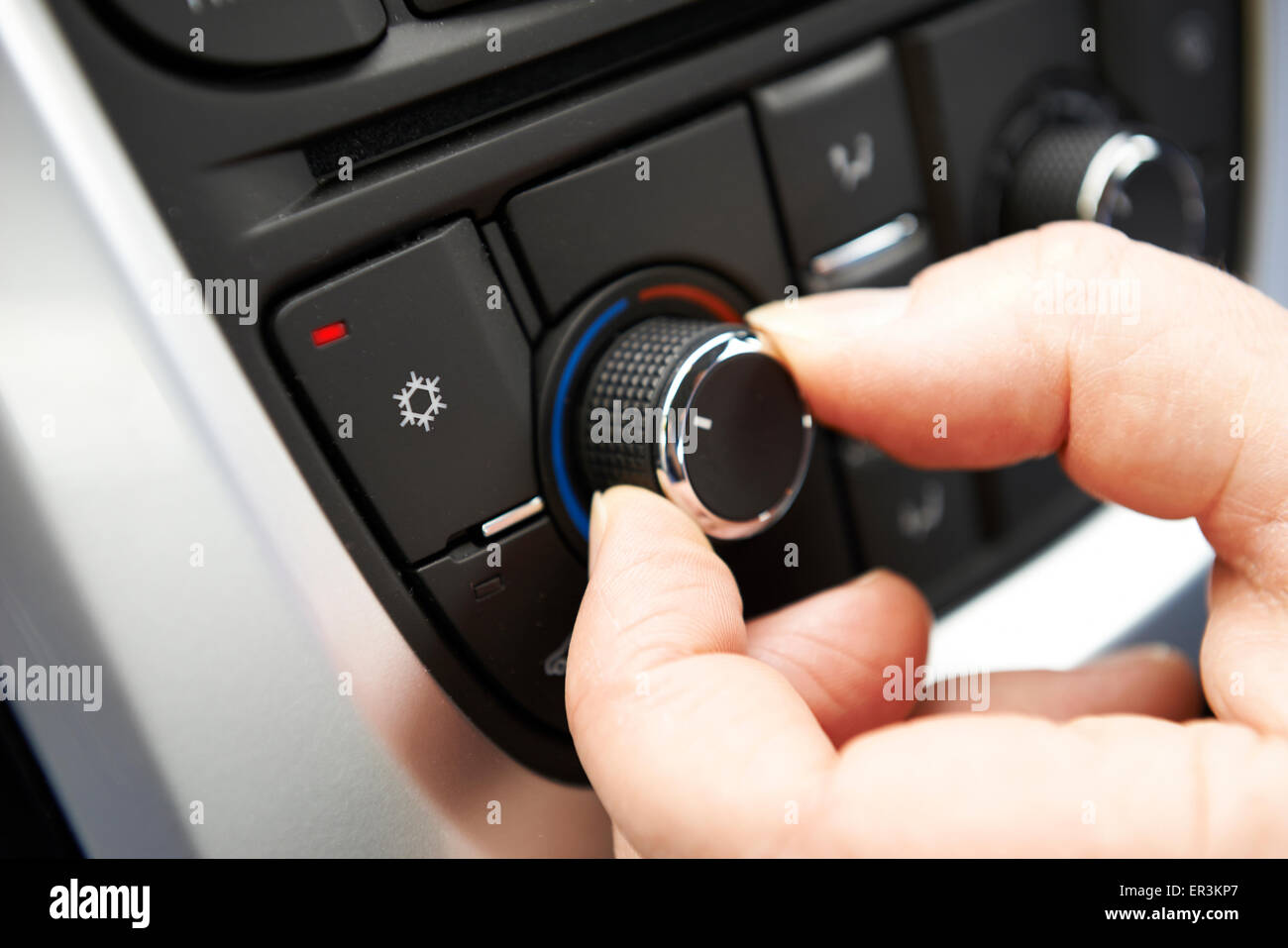 Close Up Of Hand Adjusting Car Air Conditioning Control On Dashboard - Stock Image
