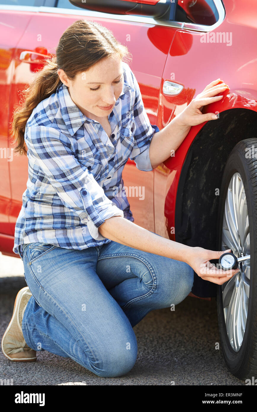 Woman Checking Car Tyre Pressure Using Gauge - Stock Image