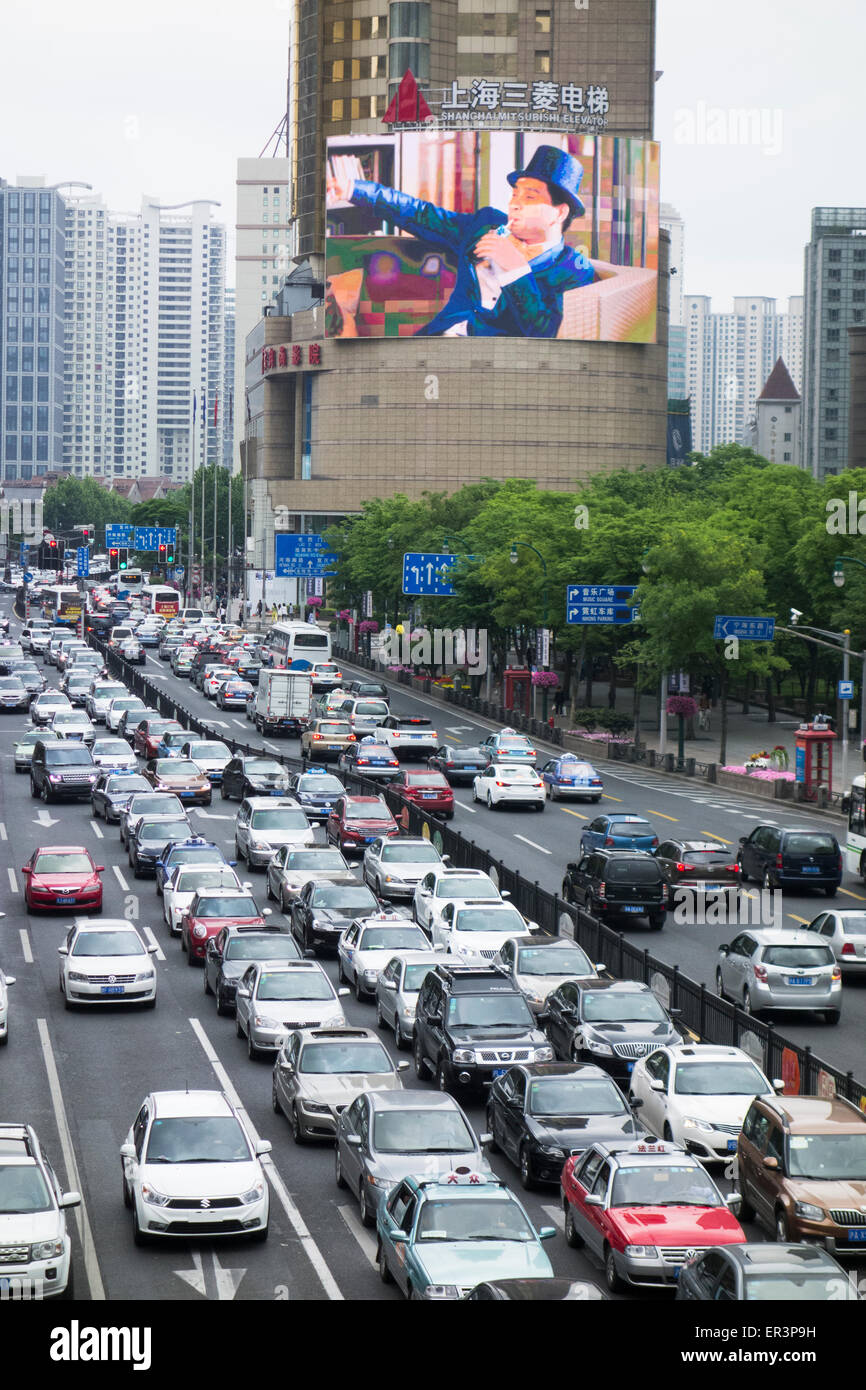 traffic and giant TV screen billboard advertising sign in downtown central city area of Shanghai China - Stock Image