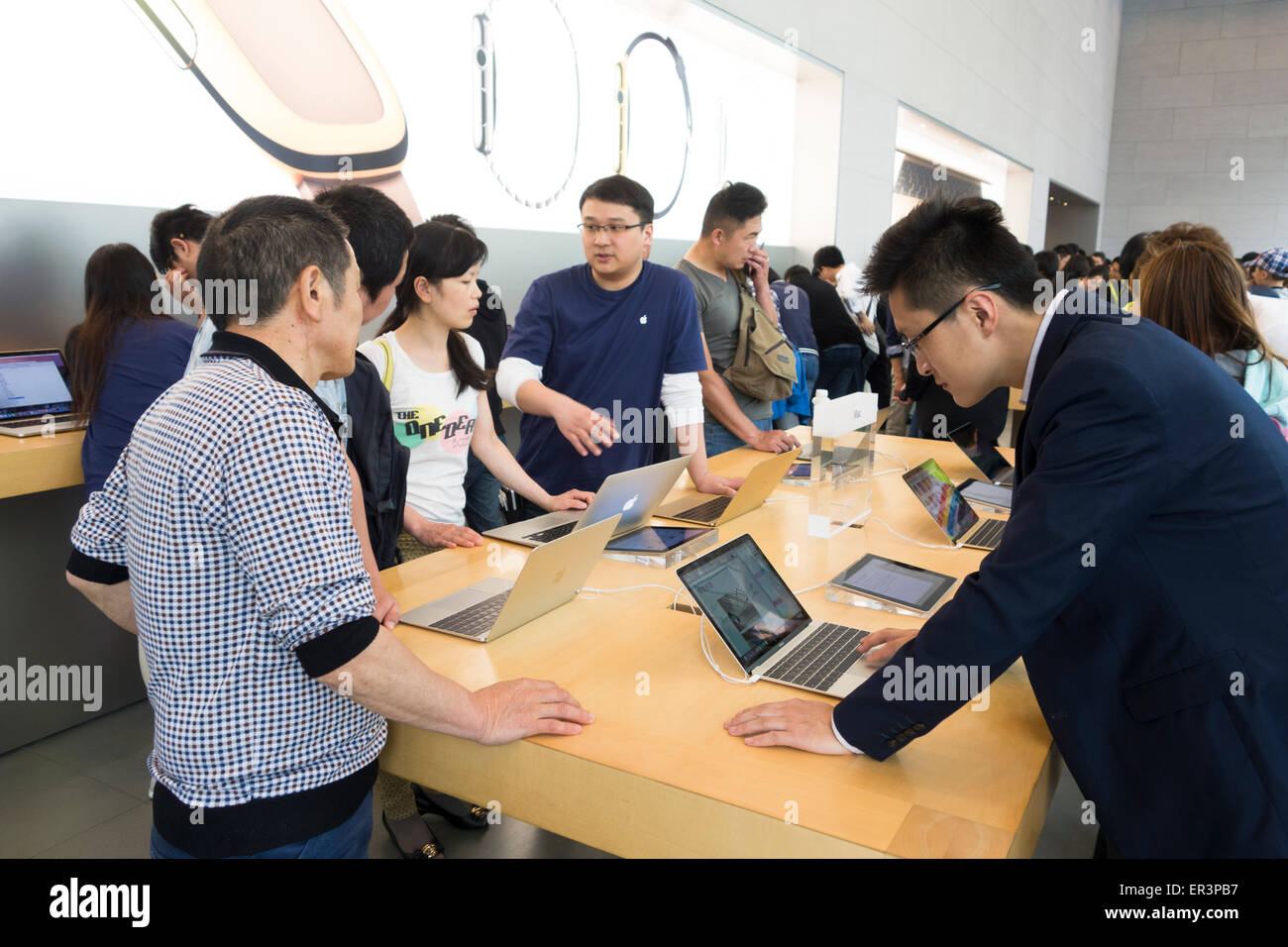 Chinese shoppers crowd the interior of the Apple store to see latest computer hardware phones and  watches in Shanghai Stock Photo