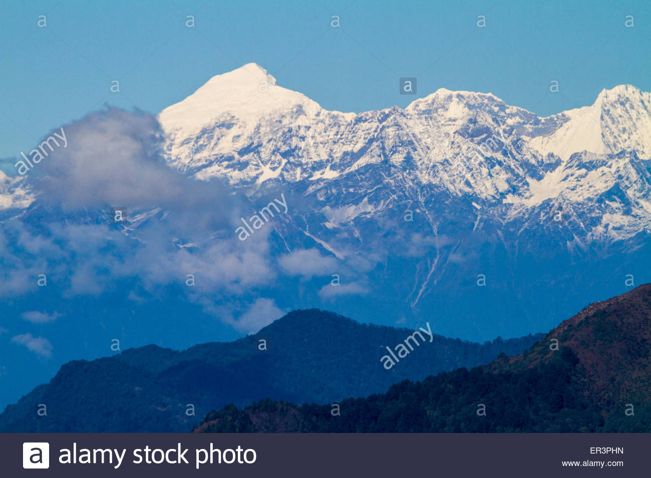 Distant Himalayan Peaks are seen from the roadside in rural Bhutan - Stock Image