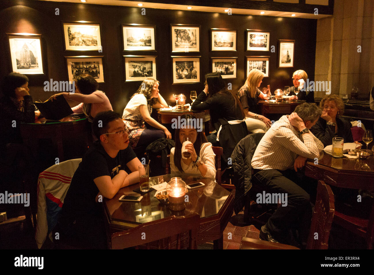 people sit at tables in cafe bar in the Peace Hotel on the Bund in downtown Shanghai China - Stock Image